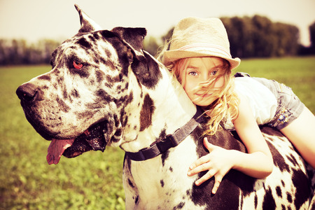 Happy little girl with her mastiff dog on a meadow in summer day. Countryside.