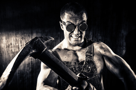 Muscular dirty coal miner with a pickaxe over dark grunge background. Mining industry. Art concept. Toned photo, old style. Фото со стока - 39282273