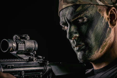 A soldier in war paint looks through the scope of automatic rifles.
