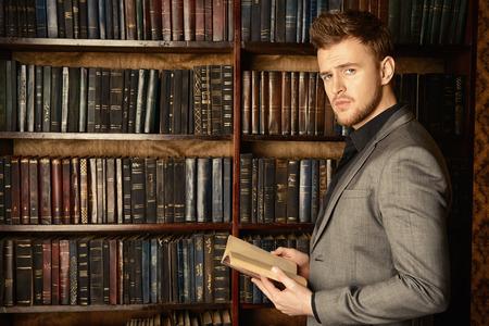 잘 생긴 좋은 옷을 입은 남자는 고전적인 인테리어 방에 책장에 의해 의미합니다. 패션. 스톡 콘텐츠