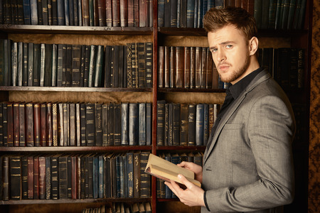 Handsome well-dressed man stands by bookshelves in a room with classic interior. Fashion. Banco de Imagens