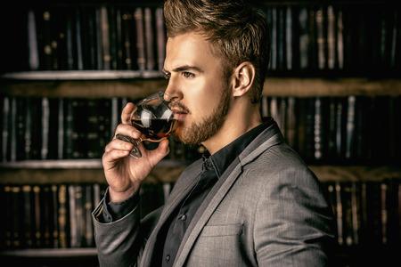 エレガントな男の飲料のガラスとの訴訟では、ビンテージ ルームに立っています。ファッション。 写真素材