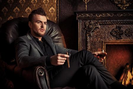 Elegancki mężczyzna w garniturze z szklanką napoju i cygarem w zabytkowe pokój. Moda. Zdjęcie Seryjne