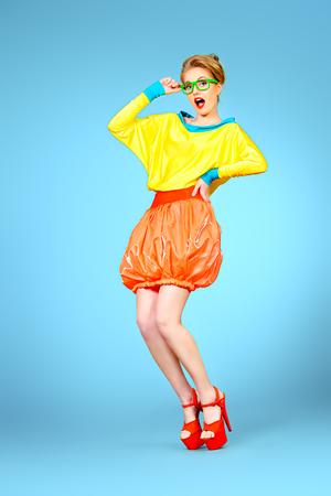 Full length portrait of a glamorous fashion model posing in vivid colourful clothes and glasses. Bright fashion. Optics, eyewear. Studio shot.