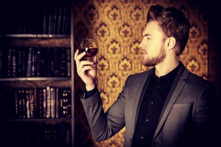 Elegant man in een pak met een glas drank en sigaar in uitstekende ruimte. Fashion.