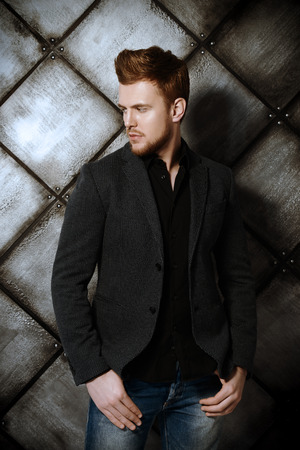 Vogue shot of a handsome man in black suit posing at studio. Mens beauty, fashion.