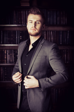 Handsome well-dressed man stands by bookshelves in a room with classic interior. Fashion. Banque d'images