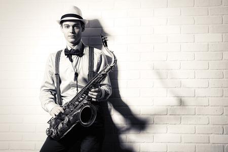 벽돌 벽에 의해 그의 색소폰 함께 서 우아한 음악가의 흑백 초상화. 예술과 음악. 재즈 음악.