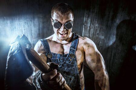 Gespierde vuile kolen mijnwerker met een pikhouweel over donkere grunge achtergrond. Mijnbouw. Art concept. Stockfoto
