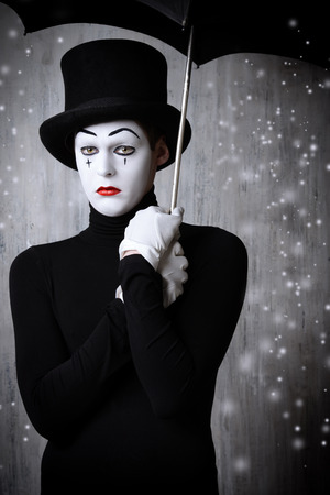 Portrait of a male mime artist standing under umbrella expressing sadness and loneliness. Grunge background. Archivio Fotografico