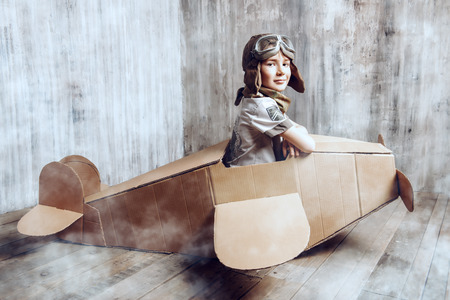 Little dreamer boy playing with a cardboard airplane. Childhood. Fantasy, imagination.