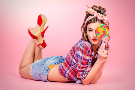 Sexy pin-up girl in shorts and high heels lying on a floor with bright lollipop over pink background. Beauty, fashion. Full length portrait.