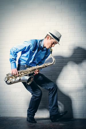 Young expressive musician playing the saxophone. Art and music. Jazz music. Foto de archivo
