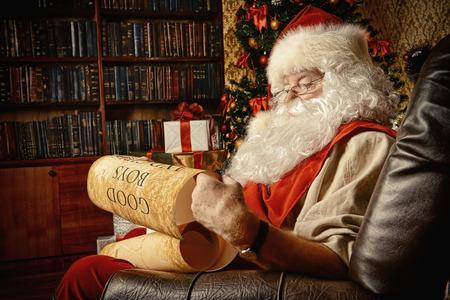 Kerstman gekleed in zijn huis kleren zitten in de kamer bij de open haard en de kerstboom. Hij leest een lijst van goede jongens en meisjes. Kerstmis. Decoratie.