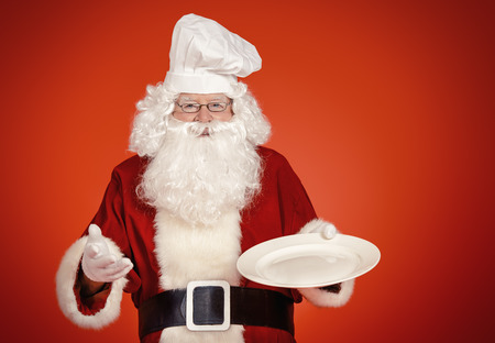 Jolly Santa Claus in a chefs hat holds a plate over festive red background. Copy space. Christmas treats.