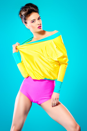 Attractive fashion model posing in vivid colourful clothes. Bright fashion. Summer style. Studio shot.