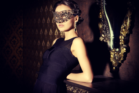 Beautiful mysterious stranger girl in venetian mask. Carnival, masquerade. Jewellery, gems. Foto de archivo
