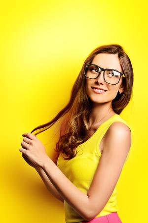 노란색 배경 위에 안경에 행복 한 젊은 여자와 밝은 노란색 드레스의 아름다움 초상화. 뷰티, 패션. 광학.