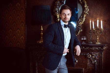 クラシック ヴィンテージ アパートでハンサムなエレガントな若い男。ファッション。高級。 写真素材