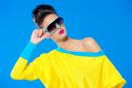 생생한 화려한 옷과 선글라스 포즈 매력적인 패션 모델입니다. 밝은 패션. 광학, 안경. 스튜디오 촬영.