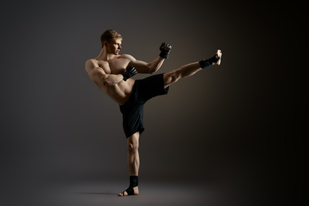 Man in sportswear performing a kick. Martial arts. Studio shot.