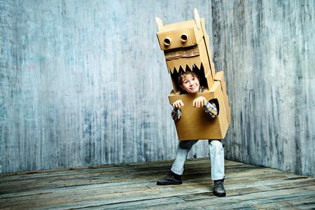 Weinig escapist jongen die met een kartonnen draak, dinosaurus. Kindertijd. Fantasie, verbeelding. Stockfoto