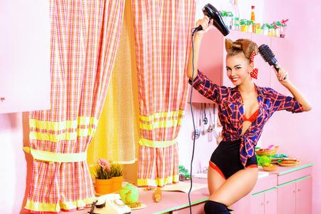 Belle fille de pin-up de faire un cheveux avec un sèche-cheveux et un peigne de sa cuisine rose. Style rétro. Mode. Banque d'images - 41428096
