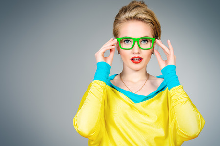 Close-up portrait of a pretty young womanl posing in vivid colourful clothes and glasses. Bright fashion. Optics, eyewear. Studio shot. Archivio Fotografico