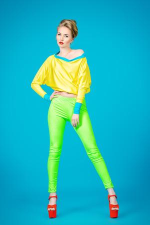 華やかなファッションのモデルが鮮やかなカラフルな服とハイヒールのプラットホームの靴の魅惑的です。明るいファッション。完全な長さの肖像