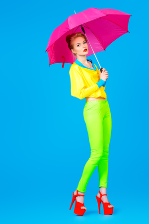 Fashionable young woman alluring in vivid colourful clothes and high heels platform shoes. Bright fashion. Pin-up style. Full length portrait.