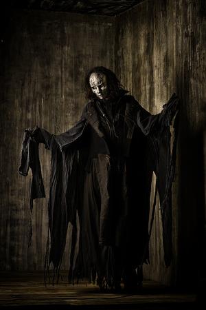 철 마스크와 검은 가운에 무서운 남자. 공상. 할로윈.