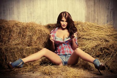 Seducente giovane donna in pantaloncini di jeans e una seducente camicia a quadri su un fieno. La moda Denim. Stile occidentale. Bellezza, moda. Archivio Fotografico - 41641816