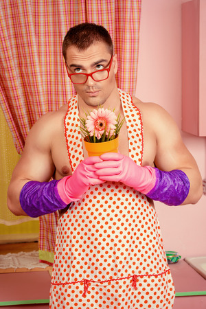 Smiling muscular man in an apron stands with a flower  in the pink kitchen. Love concept. Valentine's day. Women's day. Stock Photo
