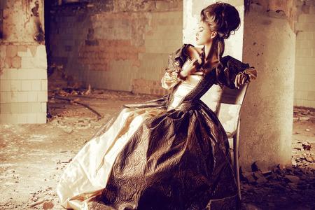 Art Fashion. Mooie jonge vrouw in elegante historische kleding en met Barocco updo kapsel stellen in de ruïnes van het kasteel. Renaissance. Barocco.