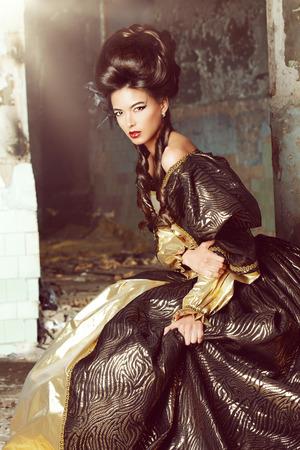 Art Fashion. Mooie jonge vrouw in elegante historische kleding en met barocco opgestoken kapsel stellen in de ruïnes van het kasteel. Stockfoto