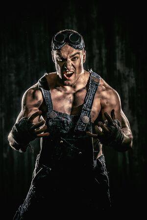 잔인 한 근육 질의 더러운 남자 검정 배경 위에 침략을 표현합니다.