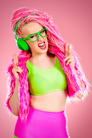 Trendy DJ party girl in bright clothes, headphones and with bright pink dreadlocks. Disco, party. Show business. Bright fashion. Фото со стока