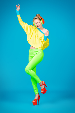 Trendy girl in bright colorful clothes listening to music in headphones and dancing. Party style. Fashion studio shot.