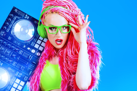 Expressive modern DJ girl wearing bright clothes, headphones and bright dreadlocks mixing up some music. Disco, party. Modern generation.