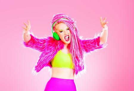 トレンディな DJ パーティーの女の子明るい服を着て、ヘッドフォンと明るいピンクのドレッドヘアを持つ。ディスコ、パーティー。ショー ビジネス