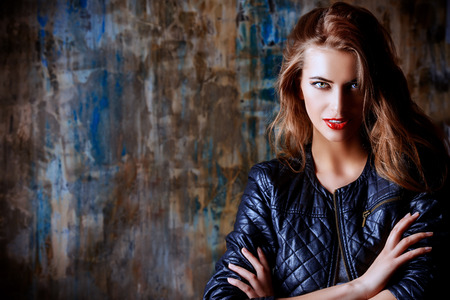 Gorgeous young woman wearing black leather jacket posing by the grunge wall. Beauty, fashion concept.