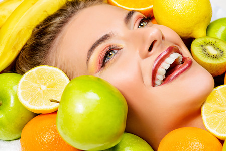 Close-up portrait of a beautiful smiling woman among fresh fruts. Healthy eating, juice. Make-up, cosmetics. Healthy teeth. Stock Photo - 41918331