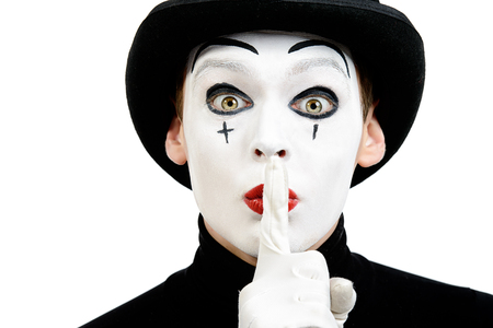 Close-up portrait of a male mime artist showing secret. Isolated over white.