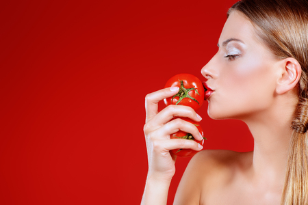 Beautiful woman trying the tomato taste. Red background. Healthy eating concept. Diet. 版權商用圖片