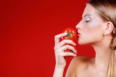 Schöne Frau, die versucht das Tomatengeschmack. Red Hintergrund. Gesunde Ernährung Konzept. Diät.
