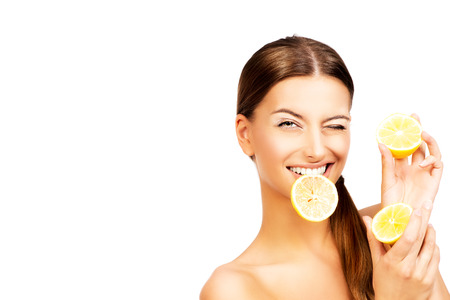 Happy smiling young woman holding fresh juicy lemons. Healthy lifestyle. Healthy eating. Fruits and vegetables. Isolated over white.