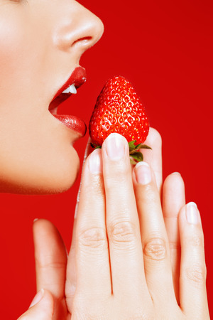 Close-up of a sexy female mouth eating fresh strawberry. Sexual lips, red lipstick. Healthy food concept. Red background. Stok Fotoğraf