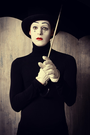 Portrait of a male mime artist standing under umbrella expressing sadness and loneliness