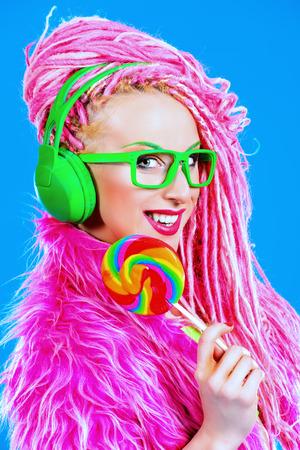 Trendy glamorous girl eating lollipop. Bright style.