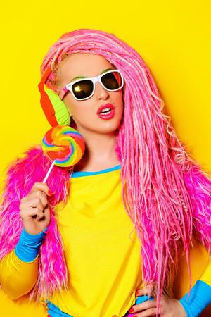 超明るい服を着て魅力的な魅力的な女の子とロリポップを食べピンクのドレッドヘア。明るいスタイル。パーティー スタイル。 写真素材